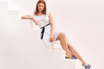 junge frau mit weißem kleid sitzt auf treppe