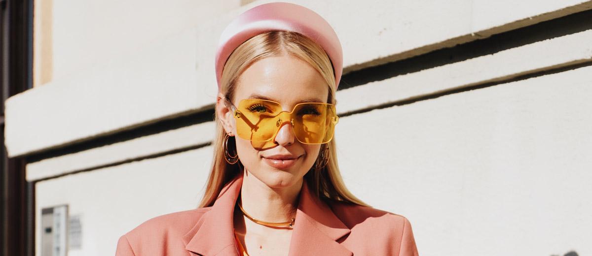 junge frau mit gelber sonnenbrille und rosafarbenem haarreif